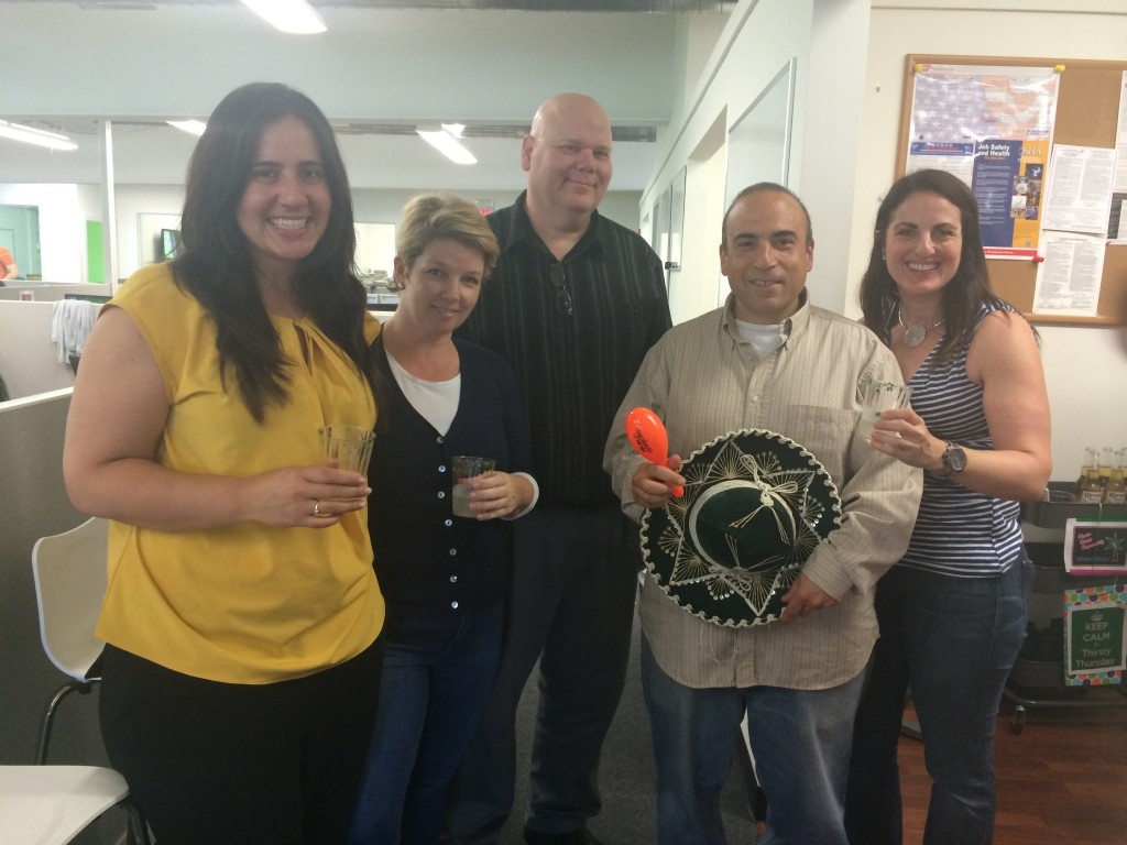 The creative team posing during a Mexican-themed happy hour (hence the sombrero)